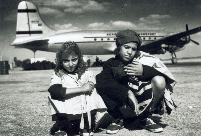 This is a historical, black and white photo of two young Yemenite Jews sitting on the tarmac with a DC-4 aircraft behind them.