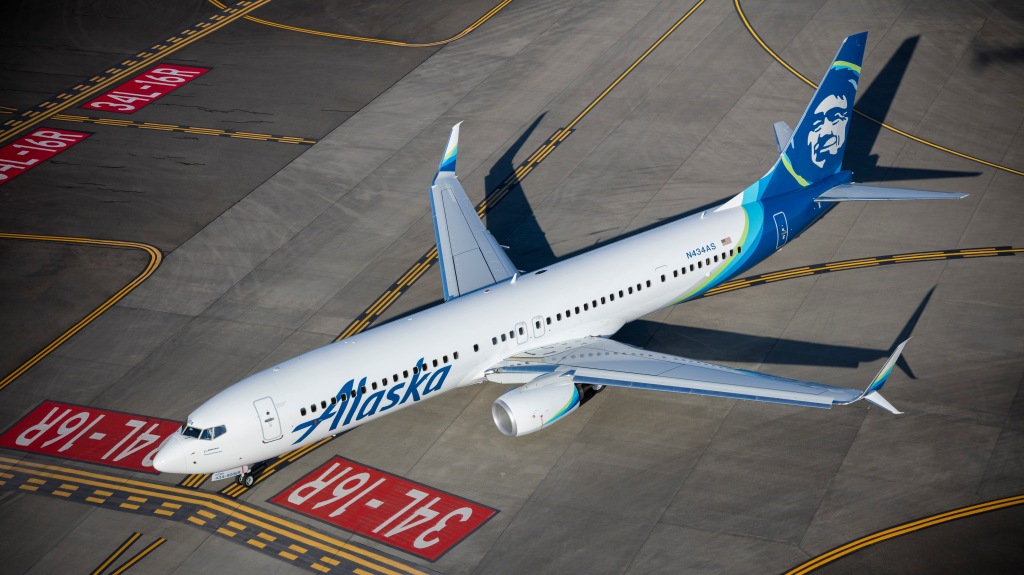 This is a photo of an Alaska Airlines jet taxiing on a runway.