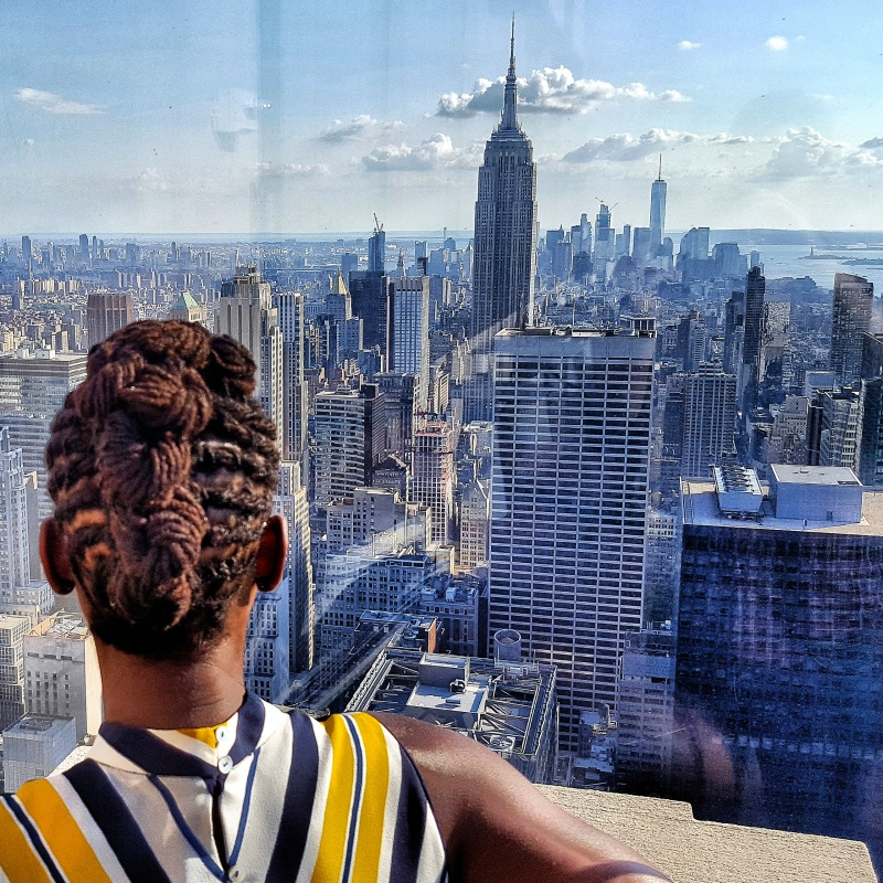 A photo of a girl looking out through glass at the Empire State Building and the Lower Manhattan Skyline.