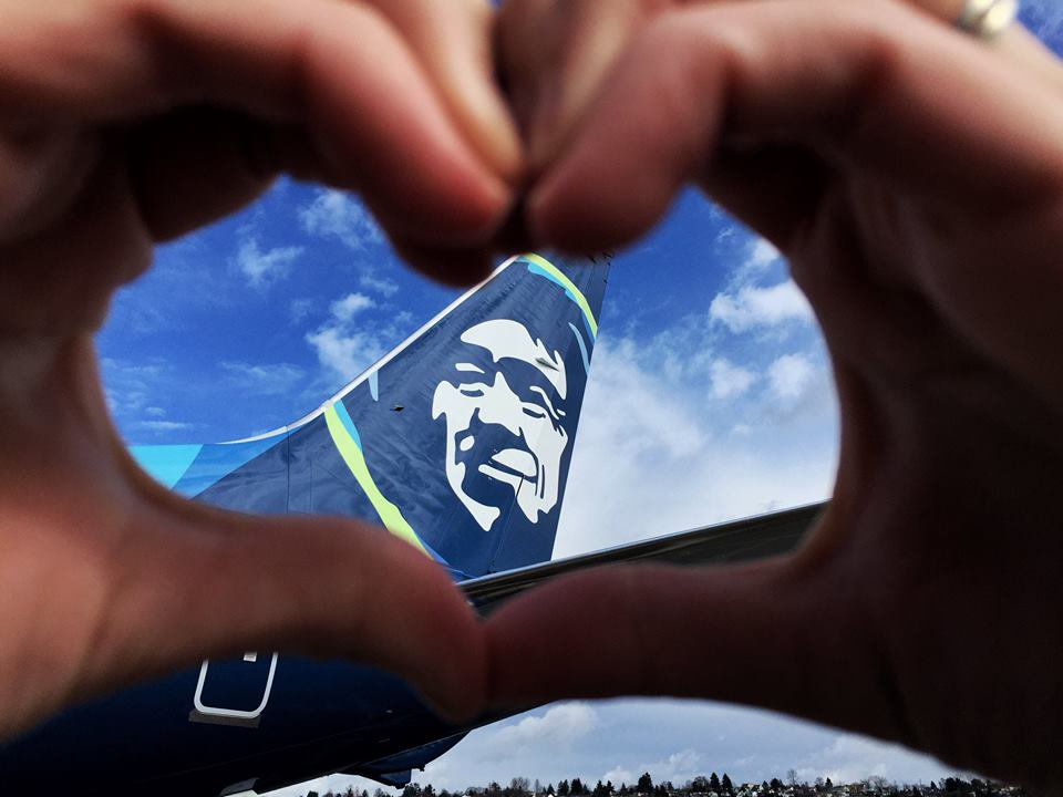 Photo of a person's hands forming a heart around the tail of an Alaska Airlines jet.