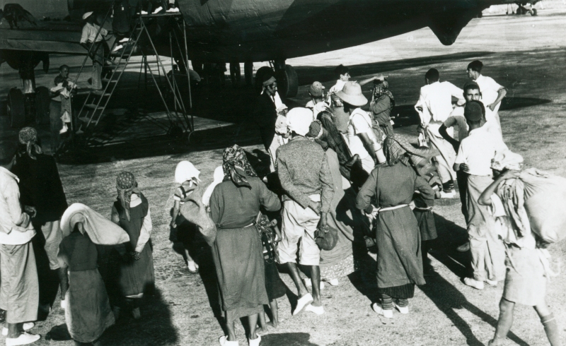 This is a historical, black and white photo of a group of about 15 Yemenite Jews gathering beside the entrance of an airplane.