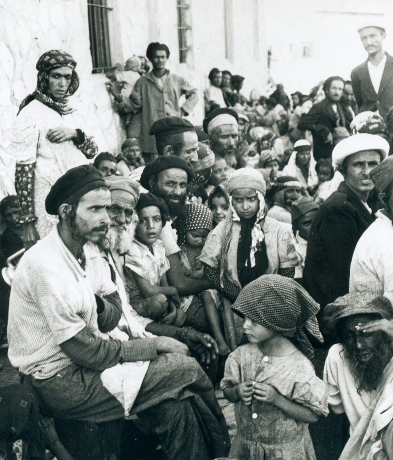 This is a historical photo in black and white print of a group of about 50 Yemenite Jews awaiting transport on the streets of Aden.