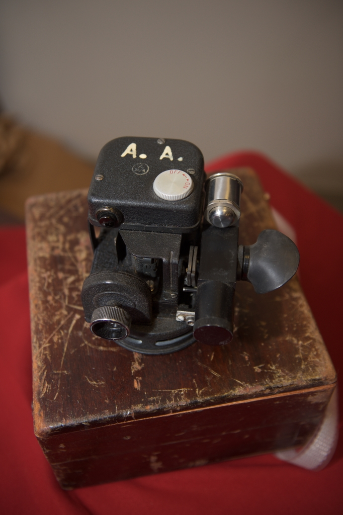 This is a photo of a black sextant sitting on top of a worn wooden box.