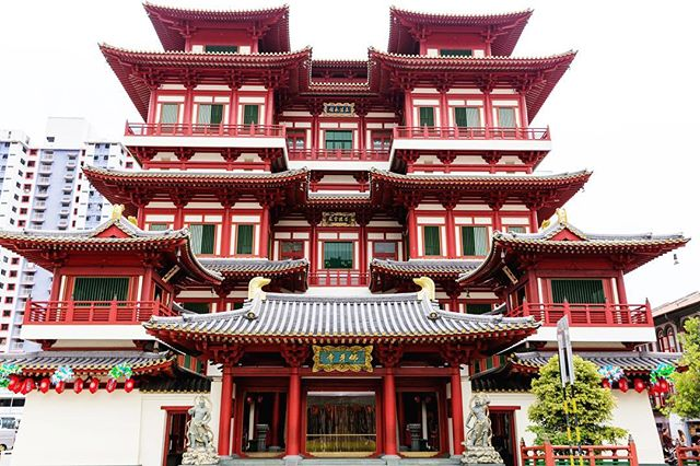 This is a photo of a Buddhist temple. The temple is red and white and has many layers.