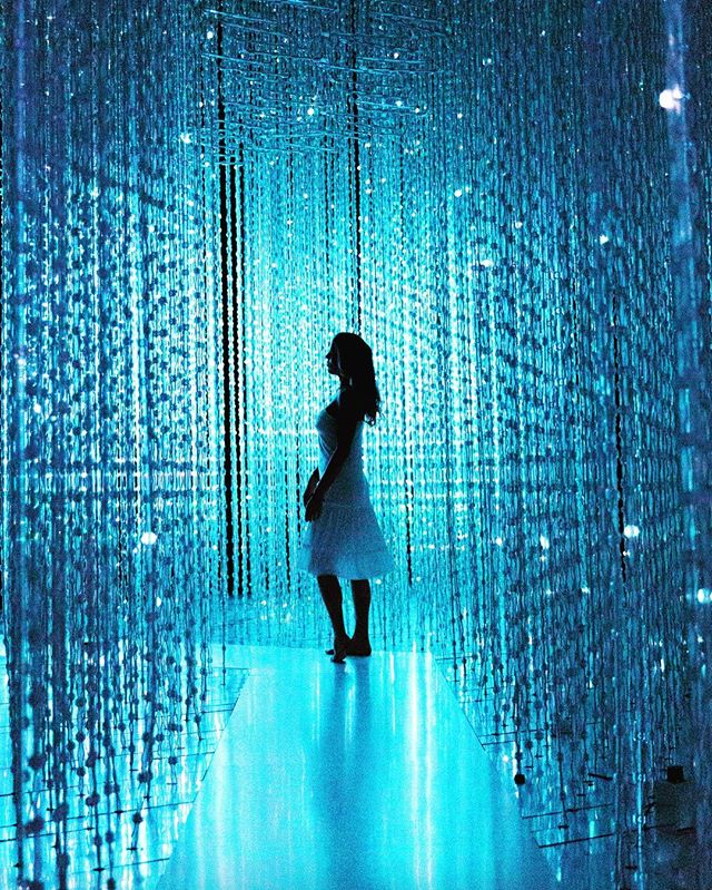 This is a photo of a girl standing in the middle of strings of blue LED lights.