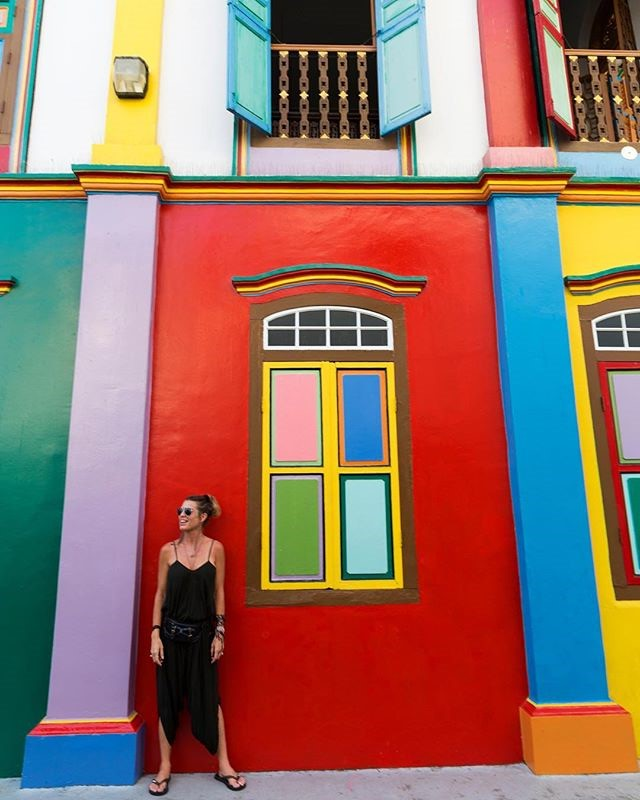This is a photo of a woman standing in front of a brightly colored rainbow building. Each column, frame is painted a different bright color.