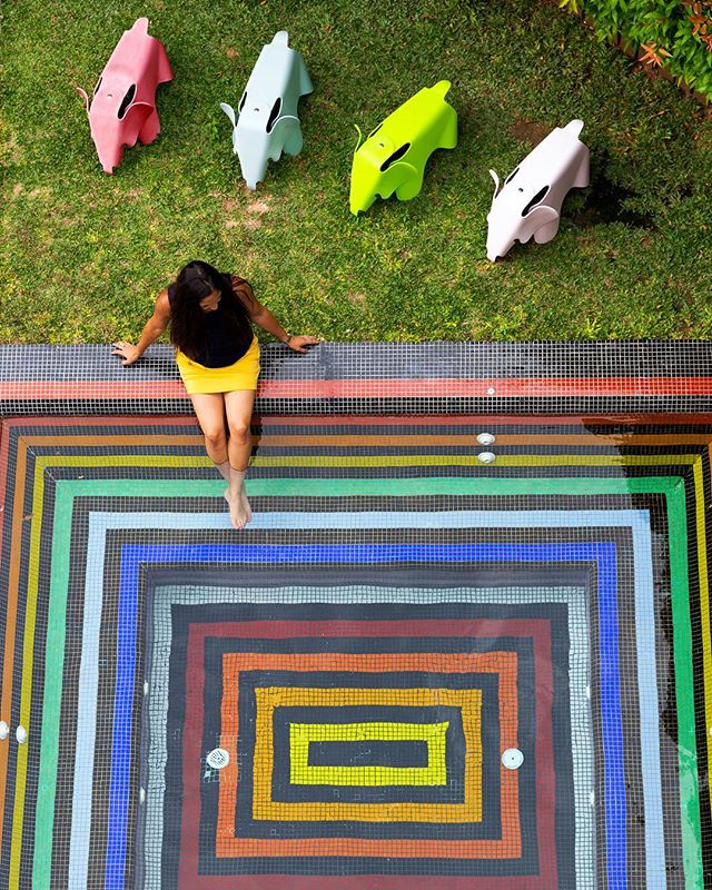This is a photo of a woman dipping her feet into a small square pool that is painted in rainbow colors.