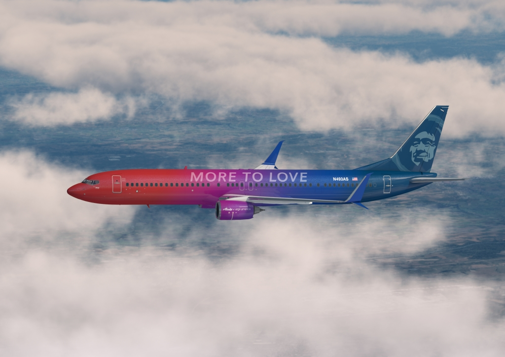 This is a photo of Alaska Airlines More to Love livery. The plane is painted with a red nose, fading into a navy blue tail