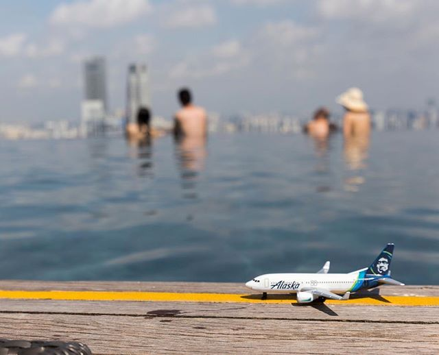 This is a photo of a mini plane overlooking an infinity pool atop the Marina Bay Sands.