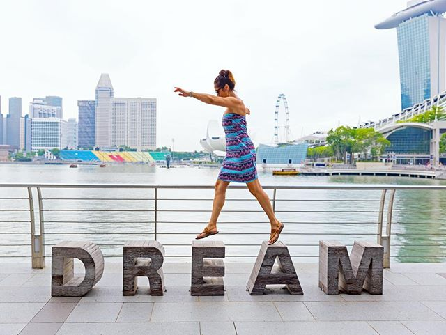 This is a photo of a girl standing on top of stone letters that spell the word DREAM.