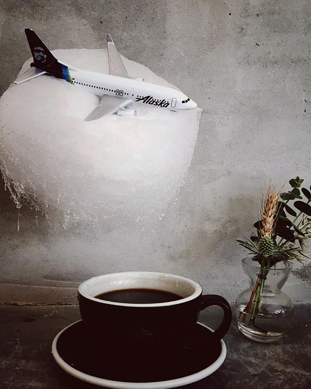 This is a photo of an Alaska Airlines mini plane embedded in cotton candy hanging over a cup of coffee.
