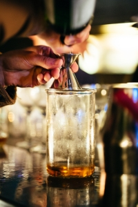 This is a photo of someone pouring a brown liquor into a glass through a strainer.