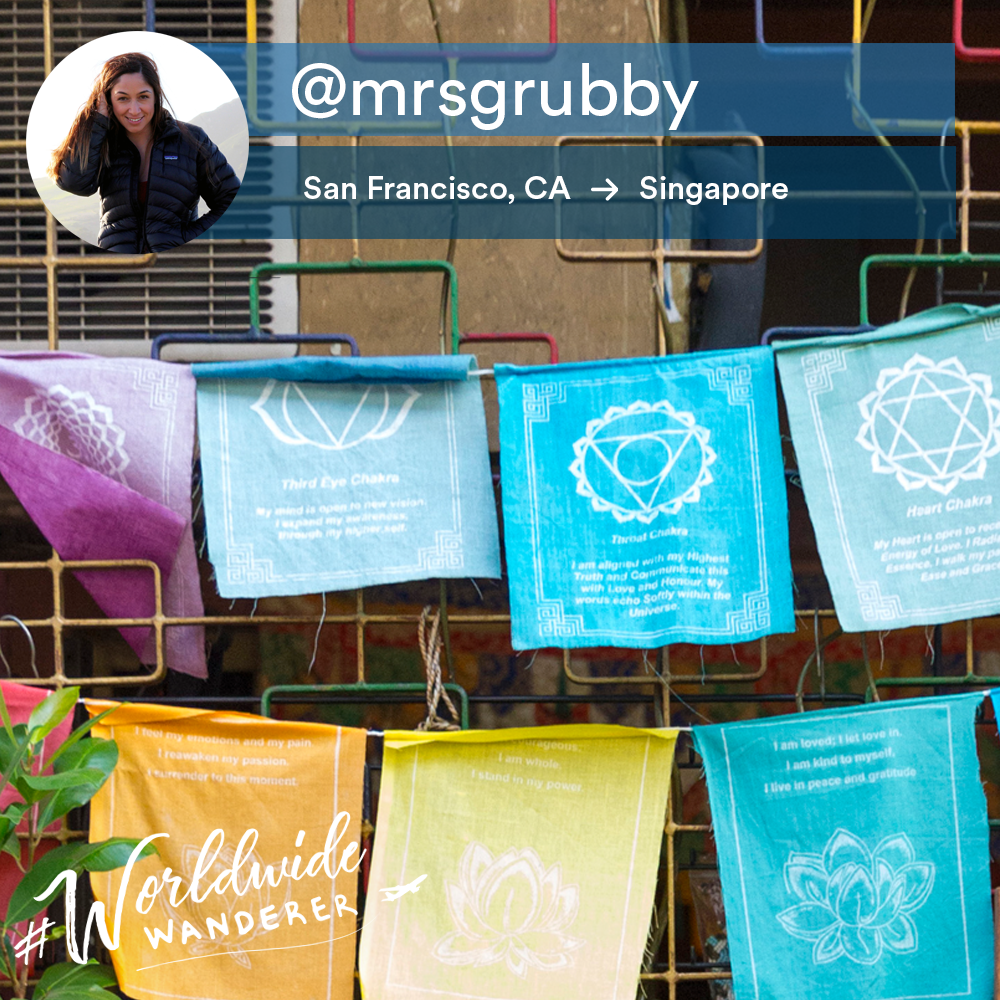 This is a photo of colorful hanging cloths with an overlay with an instagram handle.