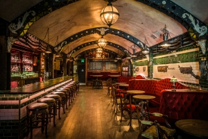 This is a photo of the Whitechapel Bar. It features wooden floors, a bar on the left with tiling and red sofas on the right. The ceiling is dome-shaped.