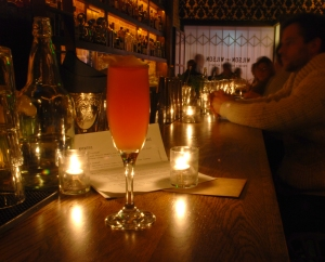 This is a photo of a pink drink sitting on top of a bar. The bar is dark with candle lighting.