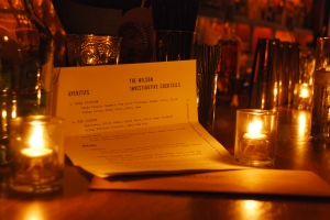 This is a photo of the paper menu sitting folded on top of the bar. The bar is dark and lit with candles.